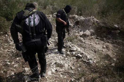 Police officers stand next to a hole, according to them, used as a mass grave, near San Fernando, Tamaulipas state, Mexico, Wednesday, April 27, 2011. Security forces have unearthed six more bodies in Tamaulipas, a northeastern Mexican border state, where a drug gang is believed to be kidnapping passengers from buses and hiding their victims in secret graves, authorities said Tuesday. Photo: AP