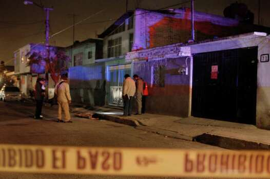 FILE - In this Feb. 13, 2011 file photo, police officers inspect the crime scene where at least 8 people were found dead after unknown gunmen opened fire at people who were standing out in the street in a working class neighborhood on the outskirts of Mexico City. For drug lords, Mexico City has been a favorite hideout and place to launder money, making the sprawling metropolis somewhat of an oasis from the cartel violence along the border and in outlying states. Now a spate of killings and decapitations never before seen have authorities batting down fears that a once-distant drug war is making its way into the capital. Photo: AP