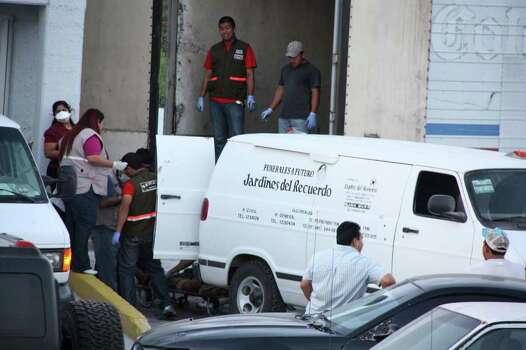 Forensic workers transfer bodies from a van into a large truck in the northern border city of Matamoros, Mexico Wednesday April, 6, 2011. At least fifty-nine bodies were found buried in a series of pits in the northern Mexico state of Tamaulipas, near the site where suspected drug gang members massacred 72 migrants last summer, officials said. Photo: AP