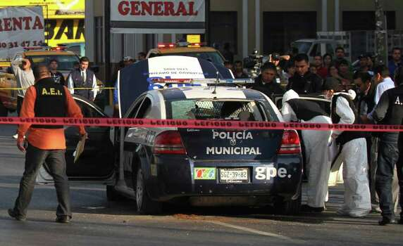 Forensic investigators and police examine a bullet-riddled municipal police patrol car in the town of Guadalupe, on the outskirts of Monterrey, Mexico, Wednesday Jan. 19, 2011. According to police authorities, two officers were gunned down by unknown gunmen in the attack. Photo: AP
