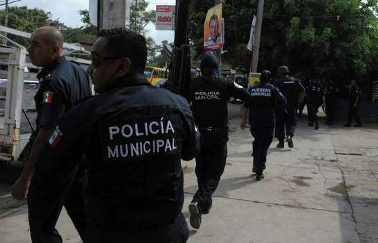 Police react as gunmen on vehicles shoot at them outside a police station in Acapulco, Mexico, Saturday, Jan. 8, 2011. This weekend got off to a bloody start with 27 people killed there from Friday evening to early Saturday, according to local police authorities. Photo: AP