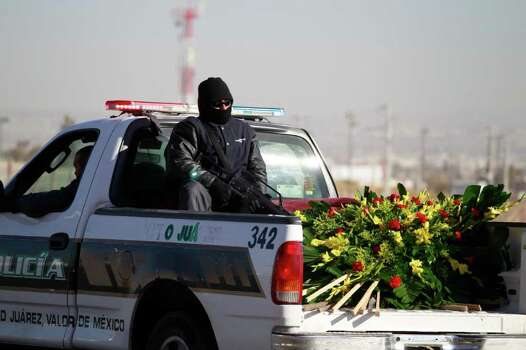 Municipal police officers take a wreath of flowers in their vehicle as they head to a funeral mass service for slain fellow officers in Ciudad Juarez, Mexico Tuesday, Dec. 7, 2010. Last Saturday, gunmen ambushed and killed 4 municipal police officers. Photo: Dario Lopez-Mills, AP / AP