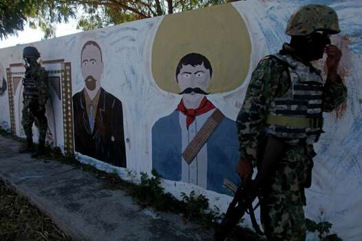 Navy marines stand next to a wall painted with portraits of Mexican Revolution heroes Emiliano Zapata, right, and Francisco I. Madero in Ciudad Mier, Mexico, near the border with Texas, Friday, Nov. 19, 2010. The villagers of Ciudad Mier have been under siege for months as powerful drug cartels battle for control of a prime drug smuggling corridor. Photo: Dario Lopez-Mills, AP / AP