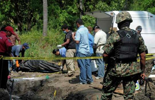 A Mexican Navy soldier watch as forensic workers remove a body which was buried at a field in the town of Tuncingo, southern Mexico, Wednesday Nov. 3, 2010. Authorities recovered at least nine bodies digging into an area mentioned in a video posted in YouTube as the burial site of 20 people of Michoacan state who were kidnapped last Sept. 30. (AP Photo/Bernandino Hernandez) marines guard the perimeter as civil protection and forensic workers dig for bodies at a clandestine that was found in the town of Tuncingo, Mexico Wednesday Nov. 3, 2010. Mexican police have recovered at least nine bodies in a mass grave identified in a narco-video as the burial site for 20 men kidnapped in the resort city of Acapulco last Sept. 30. Photo: Bernandino Hernandez, AP / AP