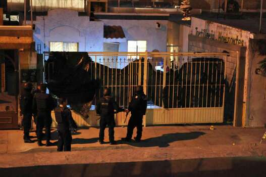 Mexican federal police officers stand outside a home after the exterior gate was covered with a plastic tarp in the northern city of Ciudad Juarez, Mexico, late Friday Oct. 22, 2010. At least 13 young people were shot dead and 15 wounded in an attack on this house during a party in Ciudad Juarez, the second such massacre in less than a week in the violent border city. Photo: Raymundo Ruiz, AP / AP