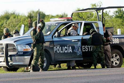 MEXICO – With a history of cartel involvement by local, state and federal law enforcement agencies, Mexican army soldiers inspect Nuevo Leon state police at the entrance to a ranch just west of Ceralvo, Mexico, Wednesday, Sept. 29, 2010. The army responded to a call of men holding kidnap victims at the ranch and a gunfight broke out when they arrived. Four of the kidnappers were killed and four of the victims were rescued. According to Gen. Cuauhtemoc Antunes, the victims were laborers from the Ceralvo area. JERRY LARA/glara@express-news.net Photo: JERRY LARA, San Antonio Express-News / glara@express-news.net