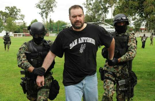 "In this photo released by Mexico's Navy, Navy marines arrest alleged drug kingpin Sergio Villarreal Barragan, alias ""El Grande,"" center, in Puebla, Mexico, Sunday Sept. 12, 2010.  Mexican marines captured Villarreal, a presumed leader of the embattled Beltran Leyva cartel who appears on a list of the country's most-wanted fugitives, in a raid Sunday, the government said. Photo: AP / Mexican Navy"