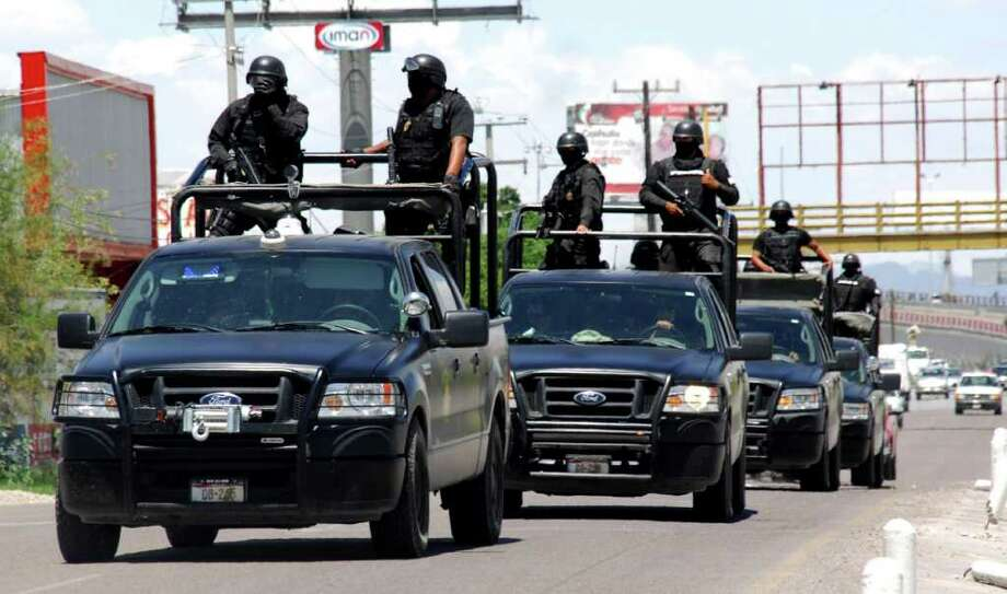 Police officers patrol a street in Torreon, in the Mexican northern state of Coahuila, Monday, July 19, 2010. Sunday gunmen interrupted a party in Torreon, killing 17 people and injuring at least 18 without saying a word, the Coahuila state Attorney General's Office said in statement. Photo: Ramon Sotomayor, AP / AP