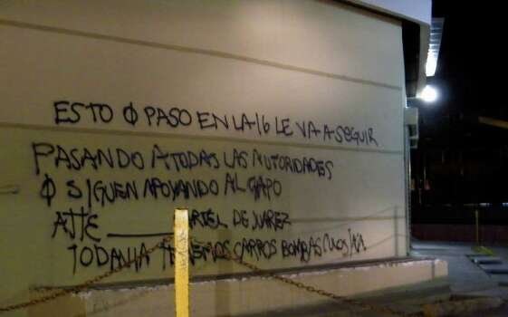 "A wall at a shopping center is covered by graffiti that reads in Spanish ""What happened on the 16 (street) is going to keep happening to all the authorities that continue to support the Chapo (Guzman), sincerely, the Juarez Cartel.  We still have car bombs (expletive) ha ha.""  Cartel assailants laid a trap for federal police and attacked them with a car bomb on Thursday the first time a drug cartel have used explosives to attack Mexican security forces, marking an escalation in the country's drug war. Photo: AP / AP"