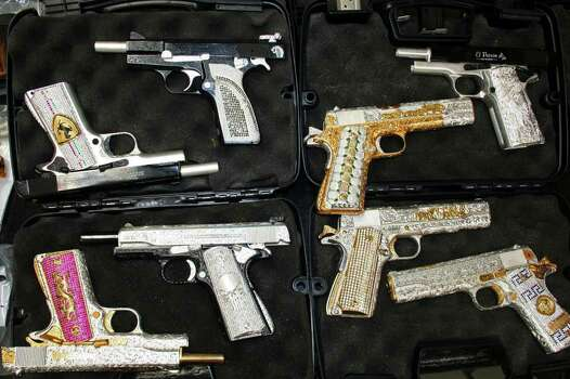 Gold-plated, diamond-encrusted weapons are shown to the press after they were confiscated when the army seized a ranch in Zapopan, Mexico, Sunday, May 2, 2010.  According to prosecutors, the weapons are believed to belong to the Valencia gang, allies of the powerful Sinaloa drug cartel, and most of the 31 pistols found in the raid had gold or silver-plated grips or glittered with diamonds. Photo: AP / AP