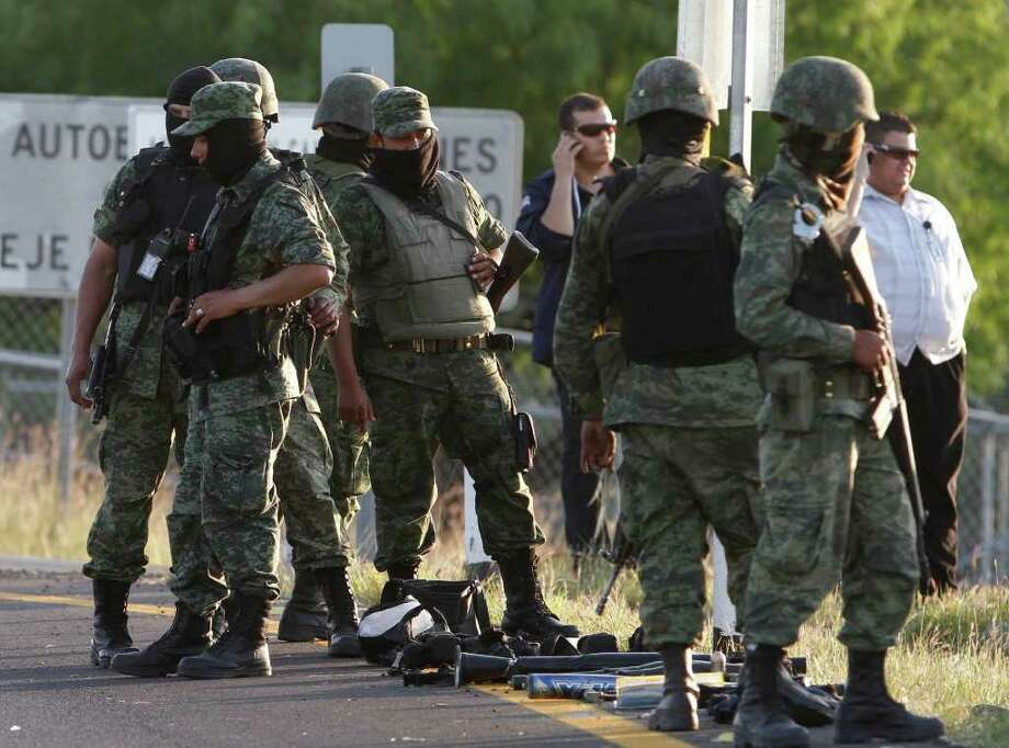 FILE - In this photo taken March 30, 2010, soldiers stand guard at the site of a firefight between gunmen and army soldiers on the outskirts of Monterrey, northern Mexico.  Photo: Claudio Cruz, AP / AP