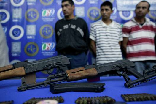 Suspects stand behind seized guns during a presentation to the press in Tijuana, Mexico, Wednesday, March 24, 2010. According to the State Police working  with the army,  six suspects busted allegedly related to the Arellano`s Felix drug cartel,  were nabbed with guns and drugs. Photo: Guillermo Arias, AP / AP