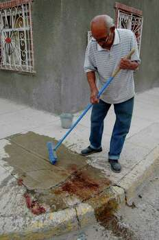 In this Thursday, Sept. 3, 2009 file photo, a resident cleans blood from the sidewalk near a drug rehabilitation center in Ciudad Juarez, Mexico. El Paso, Texas and its neighbor across the Rio Grande, Ciudad Juarez, are the Cain and Abel of the Mexican border. They are like reverse photographic images of each other. One is a model of civic order, the other an urban war zone just a few hundred yards away. Photo: AP / AP2009
