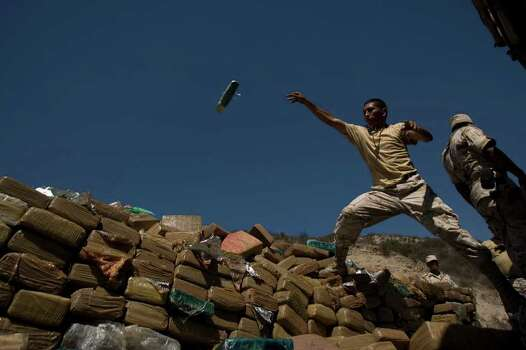 An army soldier throws a brick of marijuana on a pile of marijuana before burning it in Tijuana, Mexico, Thursday, Sept. 24, 2009. Soldiers burned more than 13 tons of seized marijuana, according to the army. Photo: Guillermo Arias, AP / AP