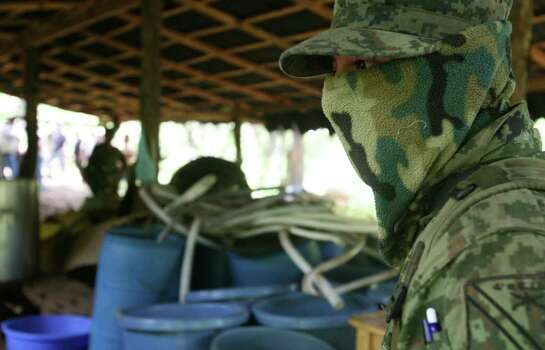"A soldier organizes a controlled explosion of a clandestine methamphetamine, or crystal meth drug laboratory, allegedly run by Mexico's ""La Familia"" drug cartel, near the town of Uruapan in Michoacan state, Mexico, Tuesday, July 28, 2009.  Federal law enforcement officials say they have seized 40 drug labs operated by the ""La Familia"" cartel which operates mostly in the region of Michoacan state, in 2009. Photo: Carlos Jasso, AP / AP"