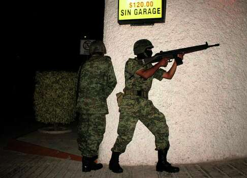 Mexican soldiers shoot their rifles during a clash between members of drug gangs and the military in Acapulco on June 6, 2009. A clash between the Mexican Army and gangs took place in the tourist zone of Cove, where condominiums, hotels, motels are located.   The Mexican government has deployed some 36,000 soldiers throughout the country in an attempt to halt the war between drug cartels, which authorities blame for the majority of the 7,700 homicides in Mexico since 2008.   AFP PHOTO / Claudio Vargas Photo: CLAUDIO VARGAS, AFP/Getty Images / 2009 AFP