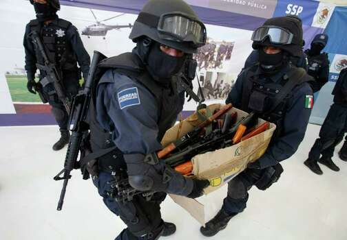 In this Feb. 10, 2009 file photo, federal police carry a box of weapons taken from suspected members of a crime gang allegedly operating on the outskirts of Mexico City after the weapons were shown to the press at the headquarters of Mexico's federal police in Mexico City.  Mexico insists the U.S. do more to stop a little-publicized form of border smuggling that is arming the world's most powerful drug cartels with U.S. assault rifles.  Cartels have killed more than 1,000 people so far this year south of the border. Photo: Dario Lopez-Mills, AP / AP