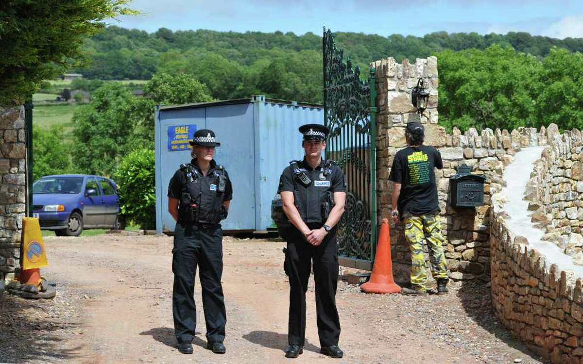 Police protect the entrance as a worker adjusts the gated entrance into singer Joss Stone's house near Cullompton, England, Wednesday June 15, 2011. British police arrested two men Monday June 13, 2011, near to the house of Joss Stone in Cullompton, southwest England, on suspicion of conspiracy to rob and murder, after residents reported a suspicious-looking vehicle. Police would not say whether 24-year-old Stone was at home when the men were arrested. (AP Photo / Tim Ireland, PA) UNITED KINGDOM OUT - NO SALES - NO ARCHIVE