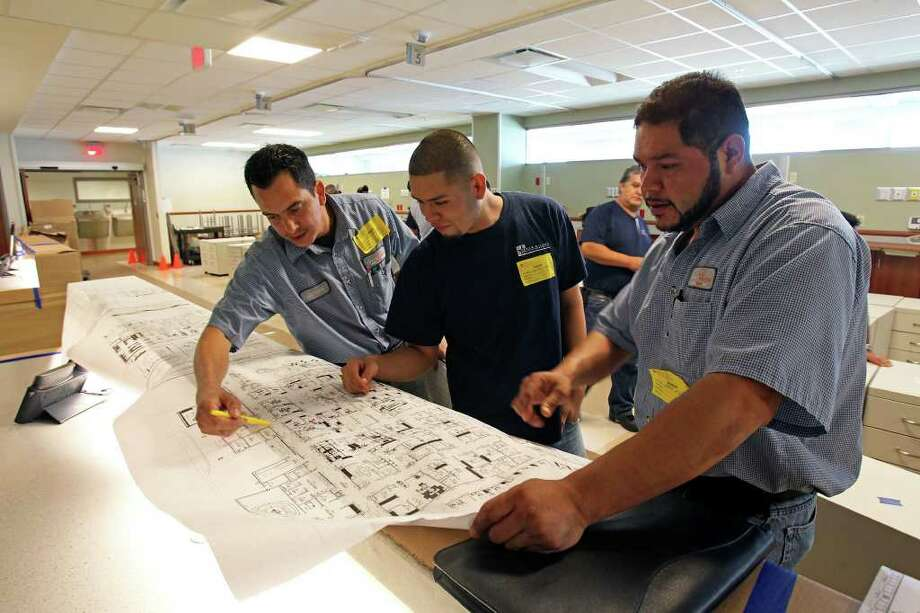 Octavio Chamorro (from left), George Moreno and Javier Monreal look at floor plans for a section of the Mission Trail Baptist Hospital. Photo: TOM REEL, SAN ANTONIO EXPRESS-NEWS / © 2011 San Antonio Express-News