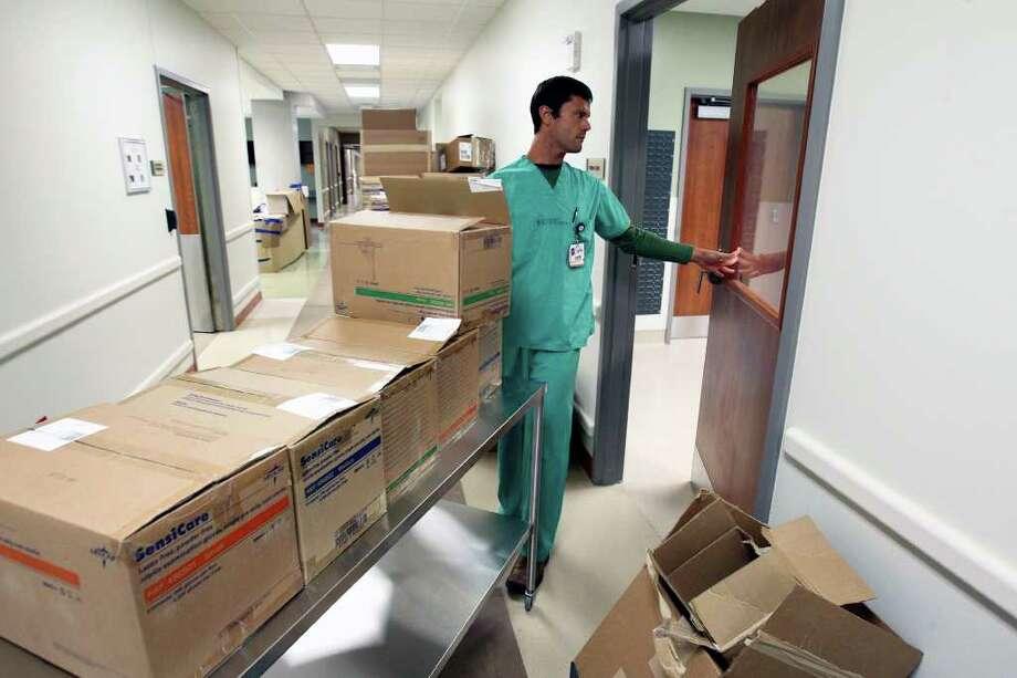 Jody Elliott moves supplies into an operating room. Photo: TOM REEL, SAN ANTONIO EXPRESS-NEWS / © 2011 San Antonio Express-News