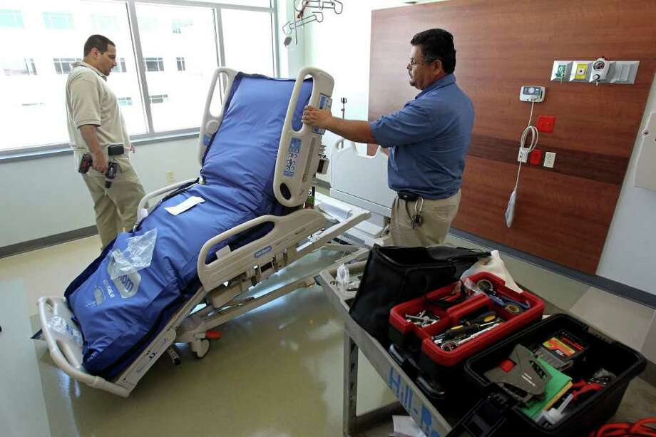 Manny Pinilla (left) and Larry Gonzalez install a hospital bed as preparation for the hospital opening nears. Photo: TOM REEL, SAN ANTONIO EXPRESS-NEWS / © 2011 San Antonio Express-News
