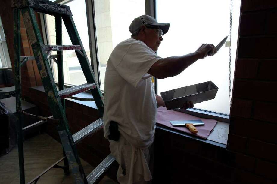 Jose Varga does some finish work on a window at the Mission Trail Baptist Hospital. Photo: TOM REEL, SAN ANTONIO EXPRESS-NEWS / © 2011 San Antonio Express-News