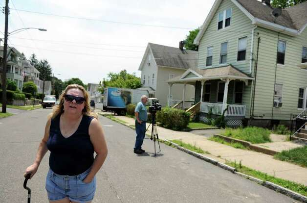 Neighbor Lori Henderson walks past 41 Hubbell Ave. in Ansonia, Conn. Wednesday, June 15, 2011.  A 5-month-old boy was killed as the result of blunt force trauma to the head. Photo: Autumn Driscoll / Connecticut Post