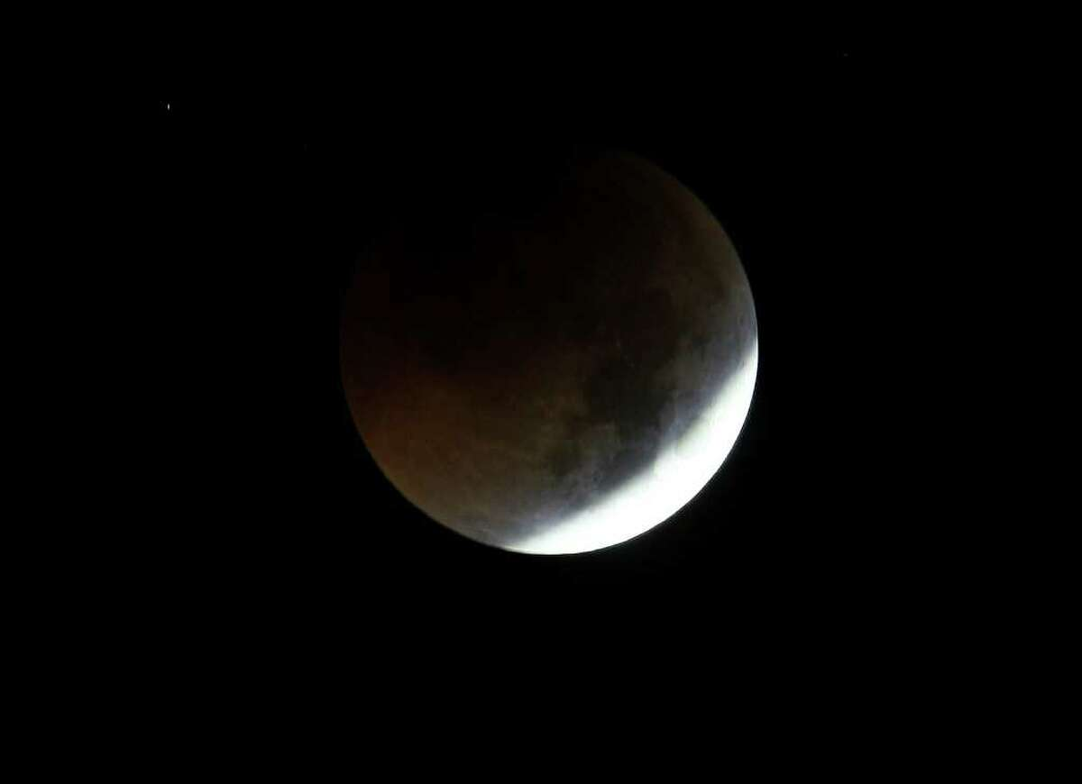 The Earth casts its shadow over the moon in a total lunar eclipse as seen in Manila, Philippines, before dawn Thursday. The total lunar eclipse was also visible in most parts of Asia.