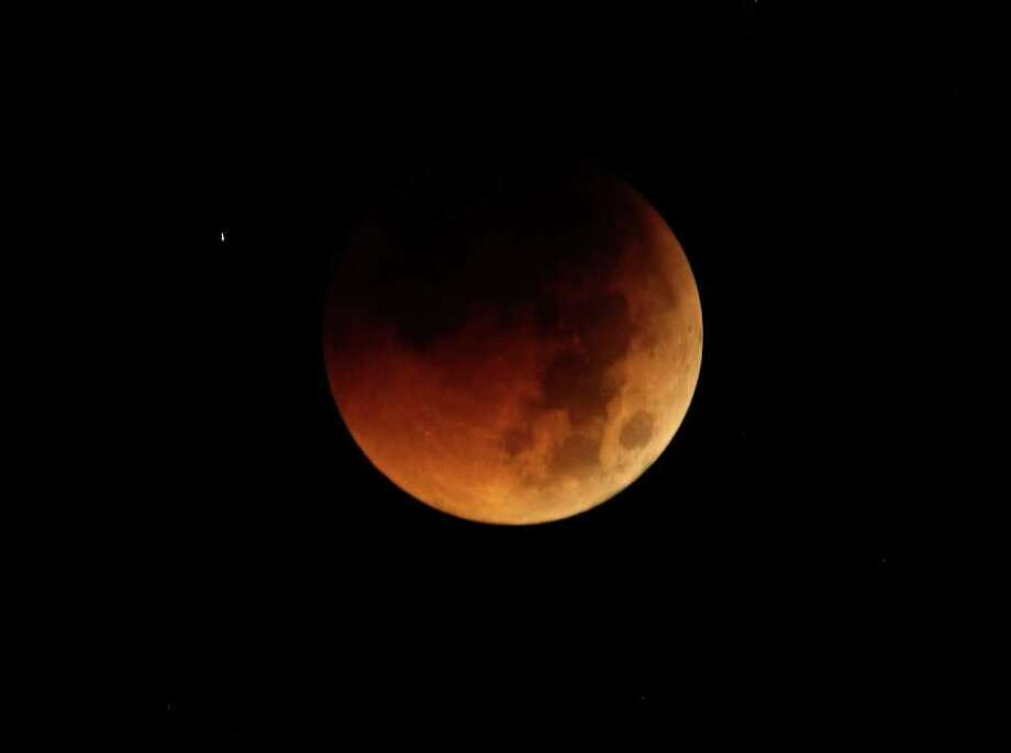 The Earth completely casts its shadow over the moon in a total lunar eclipse as seen in Manila, Philippines before dawn Thursday. The total lunar eclipse was also visible in most parts of Asia. Photo: AP