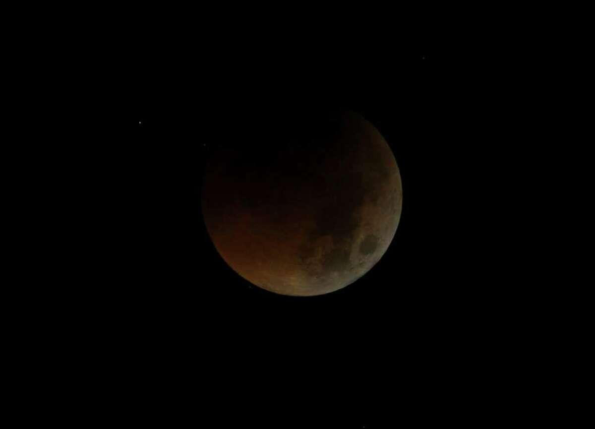 The Earth completely casts its shadow over the moon in a total lunar eclipse as seen in Manila, Philippines before dawn Thursday. The total lunar eclipse was also visible in most parts of Asia.