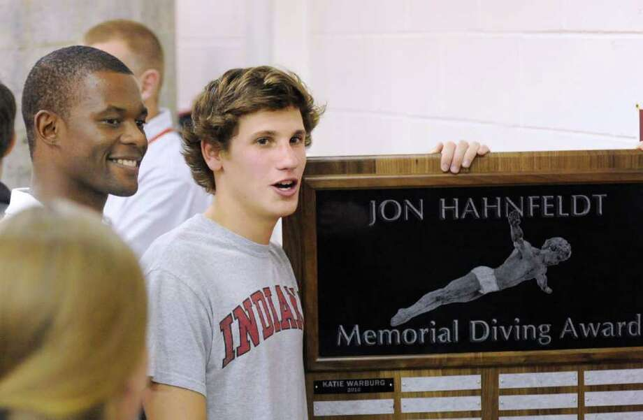 Greenwich High School FCIAC diving champion, Connor Brisson, second from right, holds up the John Hahnfeldt Memorial Diving Award, as his coach, Kevin Thompson, left, looks on during the FCIAC swimming finals at GHS, Thursday night, March 3, 2011. Photo: Bob Luckey, ST / Greenwich Time