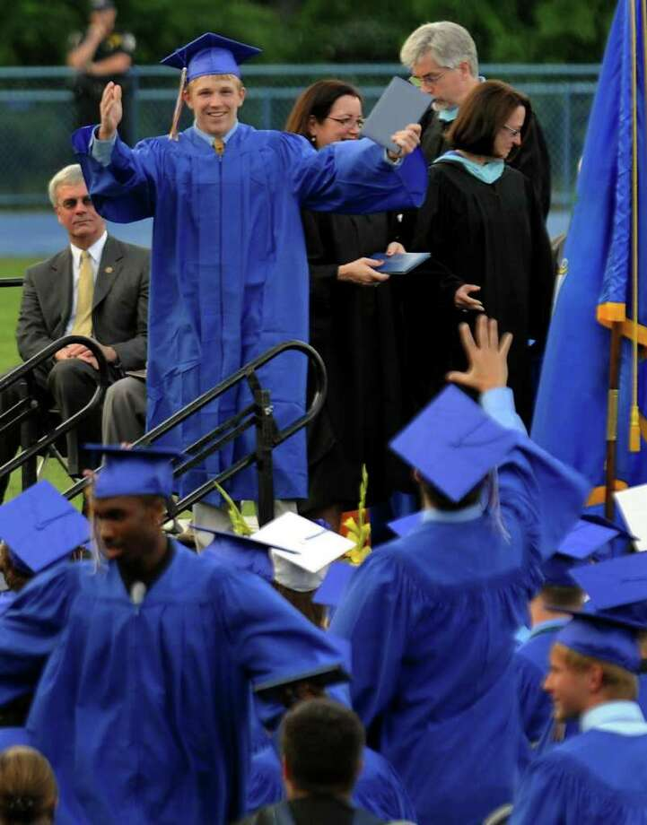 After receiving his diploma, graduate Philip Wilhelmy raises his arms in celebration as a fellow graduate waves to him during Seymour High School's 124th Commencement in Seymour, Conn. on Wednesday June 15, 2011. Photo: Christian Abraham / Connecticut Post