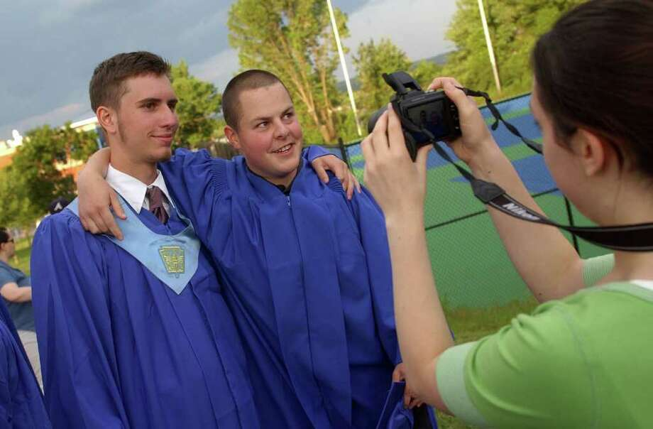 Highlights from Seymour High School's 124th Commencement in Seymour, Conn. on Wednesday June 15, 2011. Kelly Gallant, 17, takes a picture of her brother Jordan and his classmate Alex Beck, left. Photo: Christian Abraham / Connecticut Post