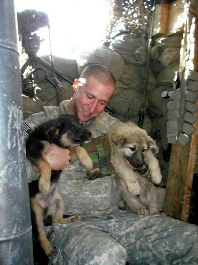 Sgt. Glenn Sewell with a pair of furry friends in Iraq. He already had served in Afghanistan. Photo: Courtesy Photo