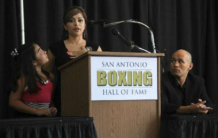 "Crystal Quiroga says her father, former world champion Robert Quiroga, would be ""very proud"" to be among the first inducted into the city's boxing shrine. Her sister, 8-year-old Catheryne Quiroga, and inductee ""Jesse"" James Leija listen to her speak at Wednesday's news conference.  LISA KRANTZ/lkrantz@express-news.net"