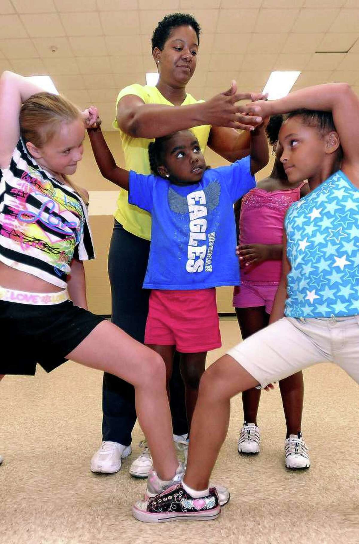 Kim Anderson helps Jasmine Smith step on Karlea Schroder, left, and Naijiaree Jones, right, during a cheerleading class at the L.L. Melton Family Life Center. Guiseppe Barranco/The Enterprise