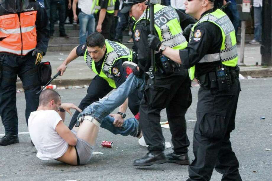 Police subdue a man following Game 7 of the NHL Stanley Cup hockey finals, in downtown Vancouver, British Columbia, on Wednesday, June 15, 2011. Photo: AP