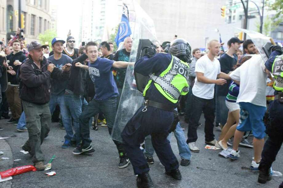 Police try to restore order after the Vancouver Canucks' 4-0 loss to the Boston Bruins in Game 7 of the NHL hockey Stanley Cup Finals on Wednesday, June 15, 2011, in Vancouver, British Columbia. Photo: AP