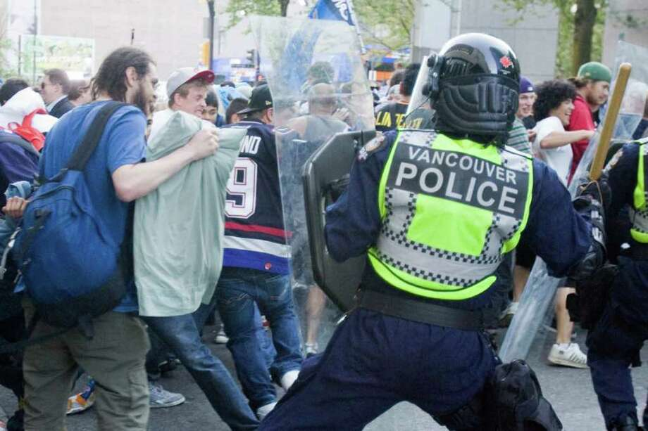Police stand in front of people on the street following Game 7 of the NHL hockey Stanley Cup Finals between the Vancouver Canucks and the Boston Bruins on Wednesday, June 15, 2011, in Vancouver, British Columbia. Photo: AP