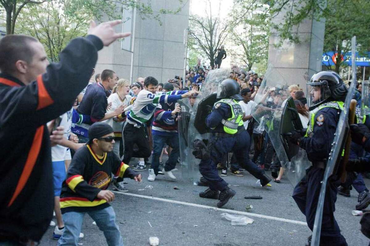 People tussled with police following Game 7 of the NHL hockey Stanley Cup Finals between the Vancouver Canucks and the Boston Bruins on Wednesday, June 15, 2011, in Vancouver, British Columbia.