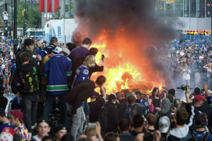 People watch a car burn following Game 7 of the NHL hockey Stanley Cup Finals on Wednesday, June 15,