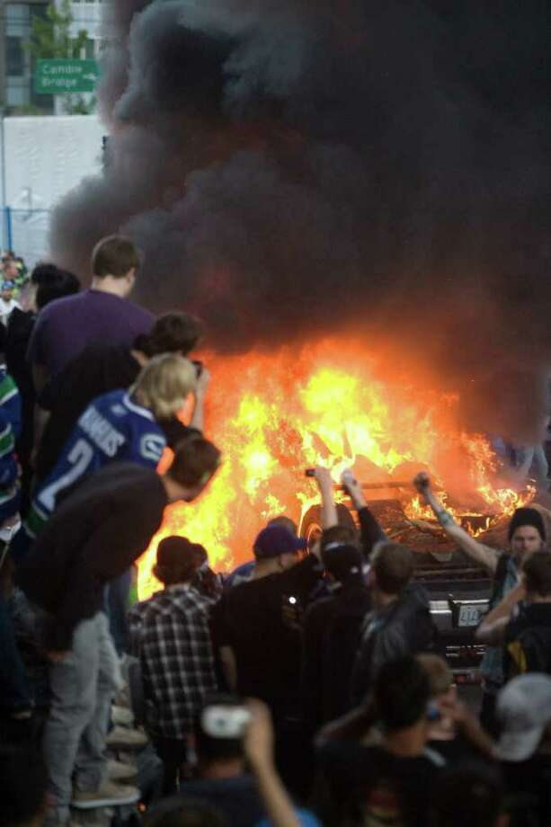 Vancouver Canucks fans watch a car burn during a riot following game 7 of the NHL Stanley Cup final in downtown Vancouver, British Columbia, on Wednesday, June 15, 2011. Parked cars were set on fire, others were tipped over and people threw beer bottles at giant television screens following the Vancouver Canucks' 4-0 loss to the Boston Bruins on Wednesday night in Game 7 of the Stanley Cup finals. Photo: AP