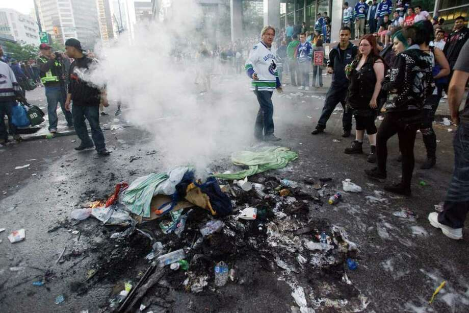 People watch a fire in Vancouver, British Columbia, on Wednesday, June 15, 2011. Parked cars were set on fire, others were tipped over and people threw beer bottles at giant television screens following the Vancouver Canucks' 4-0 loss to the Boston Bruins in Game 7 of the Stanley Cup finals. Photo: AP