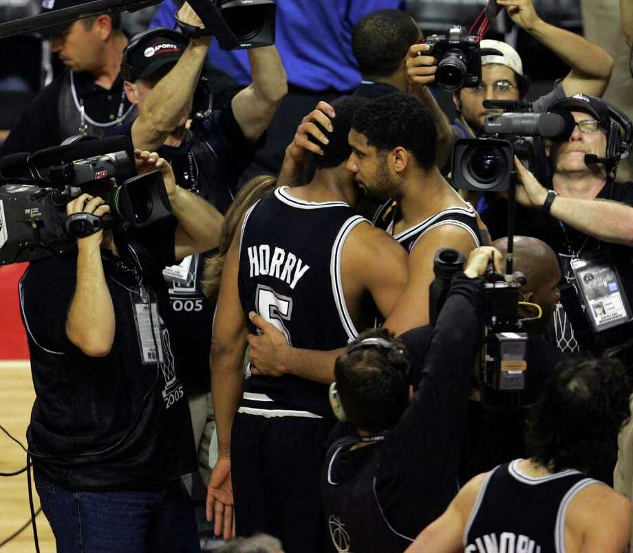 San Antonio Spurs Tim Duncan and Robert Horry hug at midcourt after beating the Detroit Pistons 96-97 during overtime game five in the NBA Finals at The Palace of Auburn Hills on Sunday, June 19, 2005. ( JERRY LARA STAFF ) Photo: JERRY LARA, Express-News / SAN ANTONIO EXPRESS-NEWS