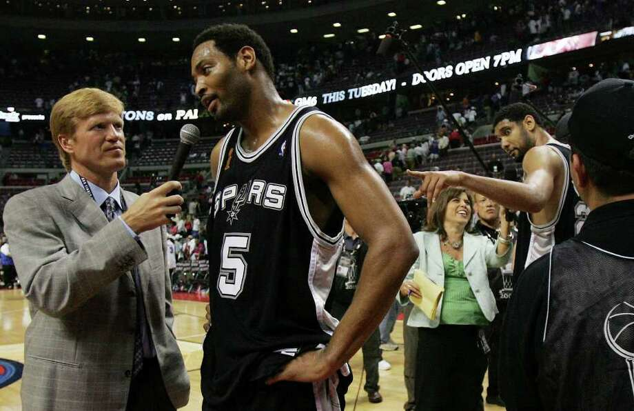 Spurs' Tim Duncan (right) gestures toward teammate Robert Horry while being interviewed by reporters after the Spurs defeated the Detroit Pistons in overtime 96-95 with the help of Horry's three-pointer during overtime action game five of the NBA Finals at The Palace of Auburn Hills near Detroit, Michigan on Sunday, June 19, 2005. (Kin Man Hui/staff) Photo: KIN MAN HUI, Express-News / SAN ANTONIO EXPRESS-NEWS
