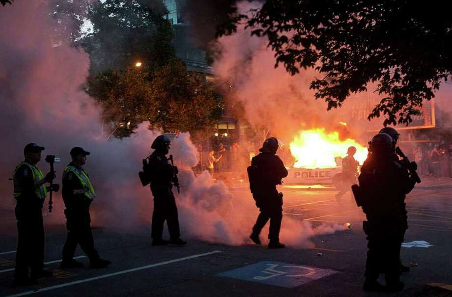 Riot police look on as two police cars burn during a riot in downtown Vancouver, British Columbia Wednesday, June 15, 2011 following the Vancouver Canucks 4-0 loss to the Boston Bruins in game 7 of the Stanley Cup hockey final.  Angry, drunken revelers ran wild Wednesday night after the Vancouver Canucks' 4-0 loss to Boston in Game 7 of the Stanley Cup finals, setting cars and garbage cans ablaze, smashing windows, showering giant TV screens with beer bottles and dancing atop overturned vehicles. Photo: AP