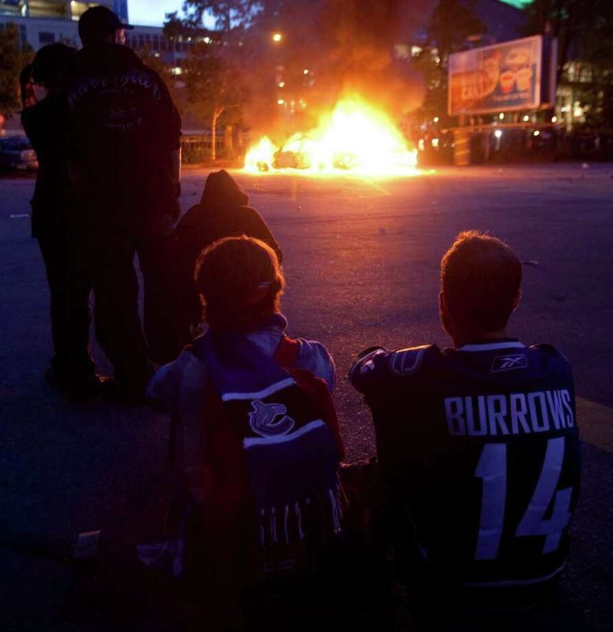 Vancouver Canucks fans watch as two police cars burn during a riot in downtown Vancouver, British Columbia Wednesday, June 15, 2011 following the Vancouver Canucks 4-0 loss to the Boston Bruins in game 7 of the Stanley Cup hockey final. Angry, drunken revelers ran wild Wednesday night after the Vancouver Canucks' 4-0 loss to Boston in Game 7 of the Stanley Cup finals, setting cars and garbage cans ablaze, smashing windows, showering giant TV screens with beer bottles and dancing atop overturned vehicles. Photo: AP