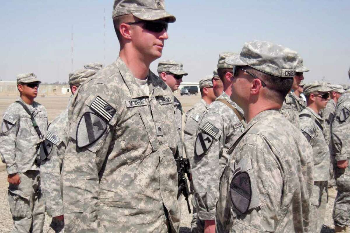 Sgt. Glenn Sewell (left) exchanges a few words with Col. Douglas Crissman after receiving a 1st Cavalry Division combat patch in Iraq.