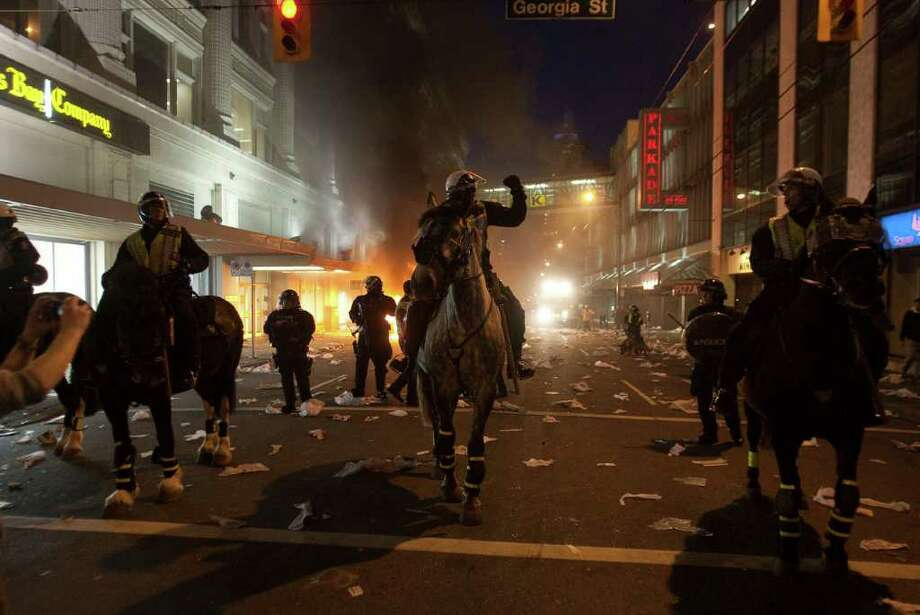 Police on horseback move down a street during a riot following the Vancouver Canucks being defeated by the Boston Bruins in the NHL Stanley Cup Final in Vancouver, British Columbia, Wednesday, June 15, 2011. Angry, drunken revelers ran wild Wednesday night after the Vancouver Canucks' 4-0 loss to Boston in Game 7 of the Stanley Cup finals, setting cars and garbage cans ablaze, smashing windows, showering giant TV screens with beer bottles and dancing atop overturned vehicles. Photo: AP