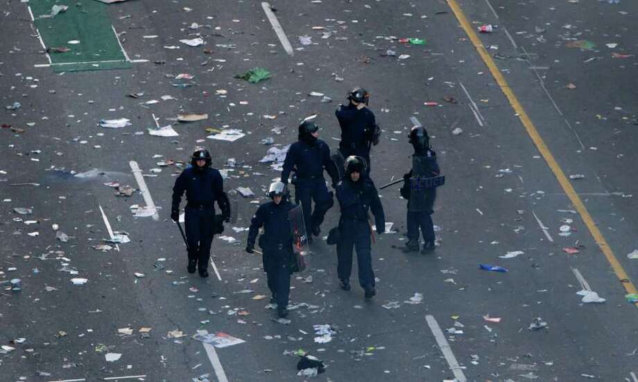 Police officers walk amongst debris after a riot broke out following the Vancouver Canucks being defeated by the Boston Bruins in the NHL Stanley Cup Final in Vancouver, British Columbia, Wednesday, June 15, 2011. Angry, drunken revelers ran wild Wednesday night after the Vancouver Canucks' 4-0 loss to Boston in Game 7 of the Stanley Cup finals, setting cars and garbage cans ablaze, smashing windows, showering giant TV screens with beer bottles and dancing atop overturned vehicles. Photo: AP